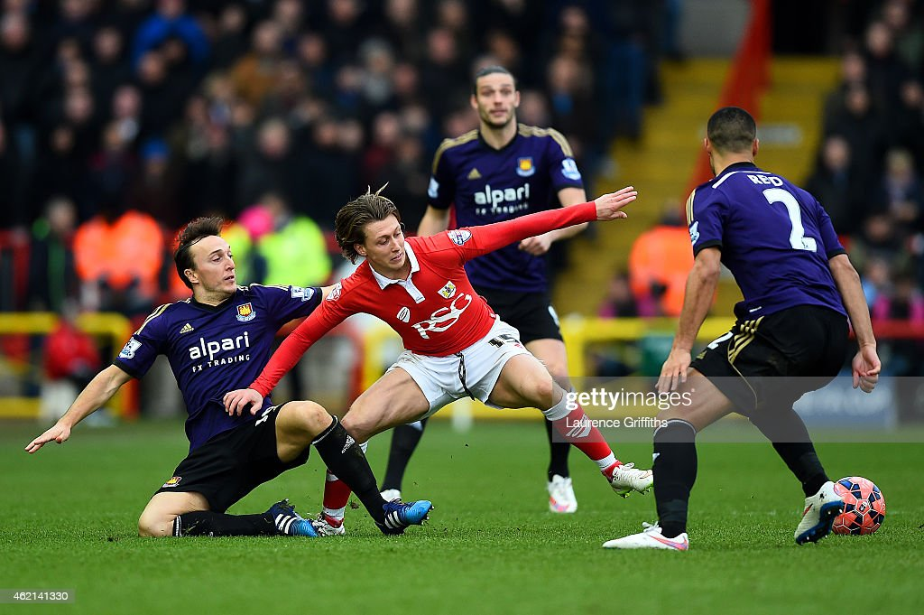 Luke Freeman of Bristol City battles for the ball with Mark Noble and Winston Reid of West Ham during the FA Cup Fourth Round match between Bristol City and West Ham United at Ashton Gate on January 25, 2015 in Bristol, England.