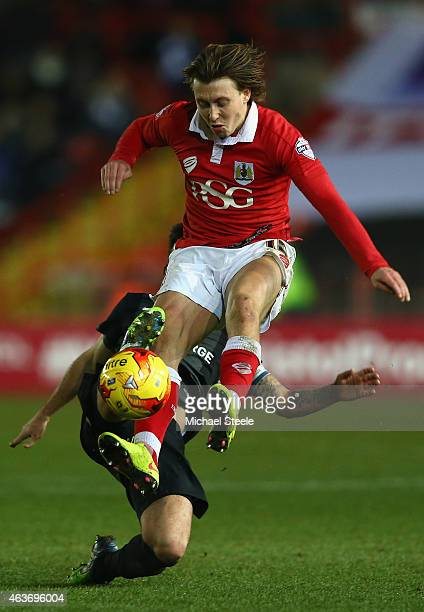 Luke Freeman of Bristol City hurdles a challenge from Michael Bostwick of Peterborough United during the Sky Bet League One match between Bristol...