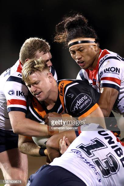 Luke Garner of the Tigers is tackled during the round 15 NRL match between the Wests Tigers and the Sydney Roosters at Leichhardt Oval on August 22,...