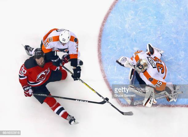 Luke Gazdic of the New Jersey Devils is checked by Samuel Morin of the Philadelphia Flyers at the Prudential Center on April 4 2017 in Newark New...