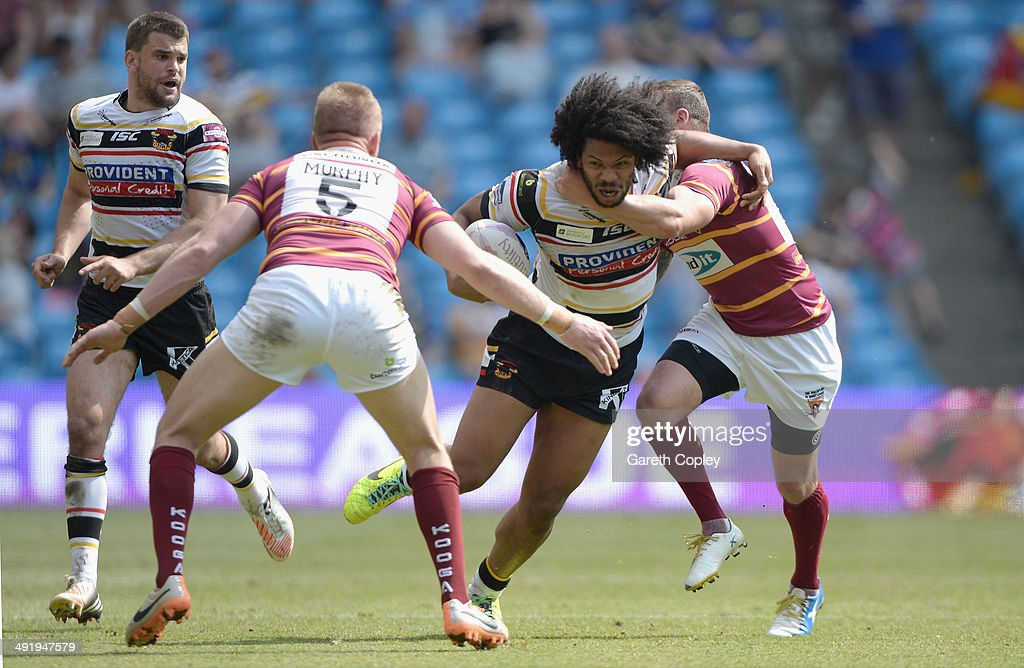 Luke George of Bradford Bulls is tackled by Aaron Murphy and Danny Brough of Huddersfield Giants during the Super League match between Huddersfield Giants and Bradford Bulls at Etihad Stadium on May 18, 2014 in Manchester, England.