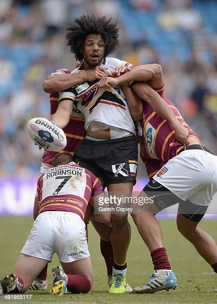 Luke George of Bradford Bulls is tackled by Luke Robinson and Leroy Cudjoe of Huddersfield Giants during the Super League match between Huddersfield...