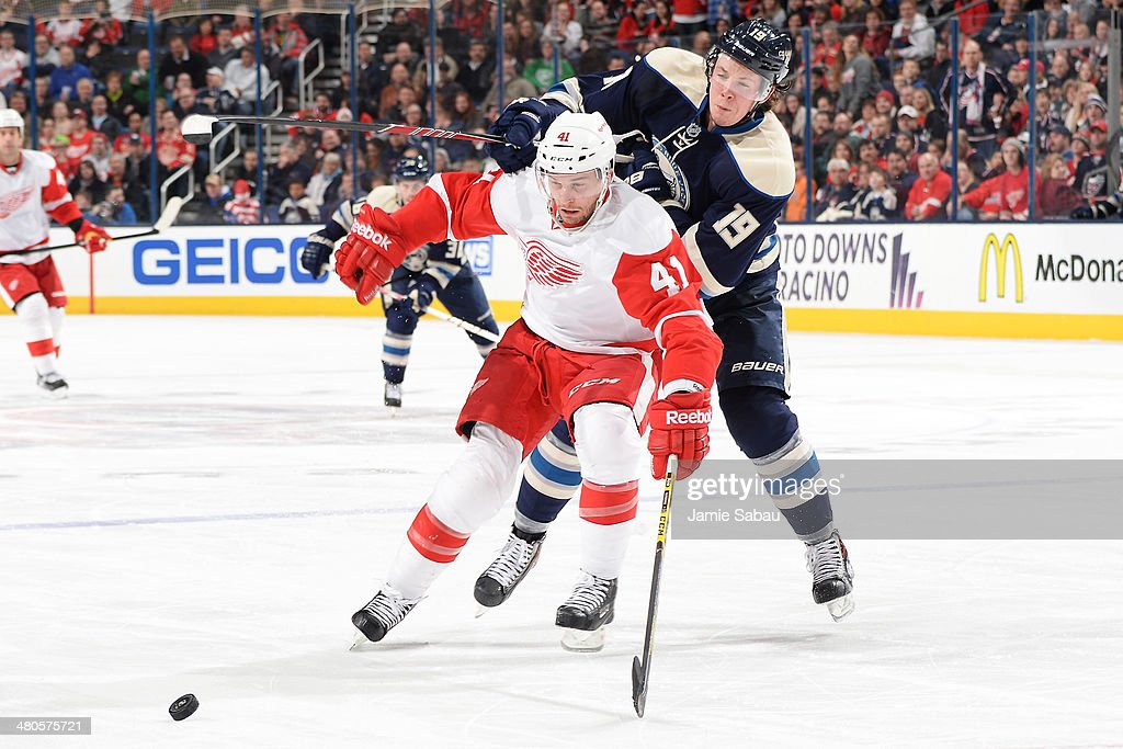 Luke Glendening #41 of the Detroit Red Wings and Ryan Johansen #19 of the Columbus Blue Jackets battle for a loose puck during the third period on March 25, 2014 at Nationwide Arena in Columbus, Ohio. Columbus defeated Detroit 4-2.