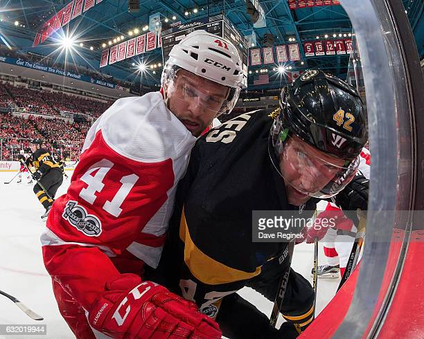 Luke Glendening of the Detroit Red Wings battles along the boards with David Backes of the Boston Bruins during an NHL game at Joe Louis Arena on...