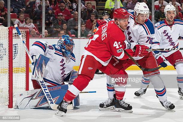 Luke Glendening of the Detroit Red Wings battles for position in front of the net with Brady Skjei of the New York Rangers while screening the view...