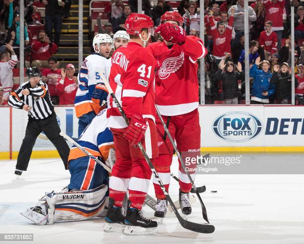Luke Glendening of the Detroit Red Wings celebrates a first period goal with teammate Riley Sheahan in front of goaltender Thomas Greiss Johnny...