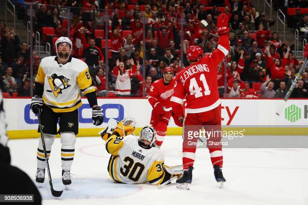 Luke Glendening of the Detroit Red Wings celebrates a second period goal next to Matt Murray and Brian Dumoulin of the Pittsburgh Penguins at Little...