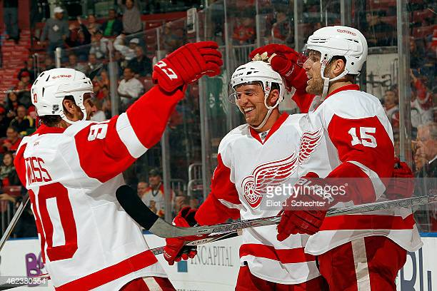 Luke Glendening of the Detroit Red Wings celebrates his goal with teammates Stephen Weiss and Riley Sheahan against the Florida Panthers at the BBT...