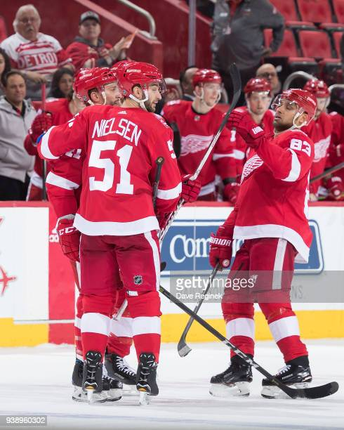 Luke Glendening of the Detroit Red Wings celebrates his third period goal with teammates Frans Nielsen and Trevor Daley during an NHL game against...