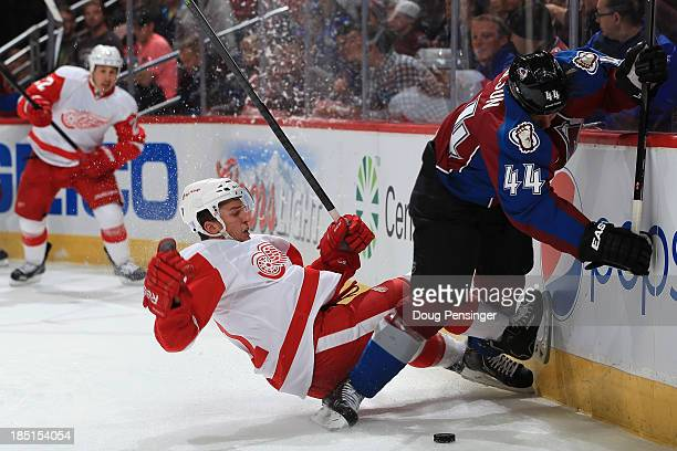 Luke Glendening of the Detroit Red Wings falls to the ice as he and Ryan Wilson of the Colorado Avalanche battle for control of the puck at Pepsi...