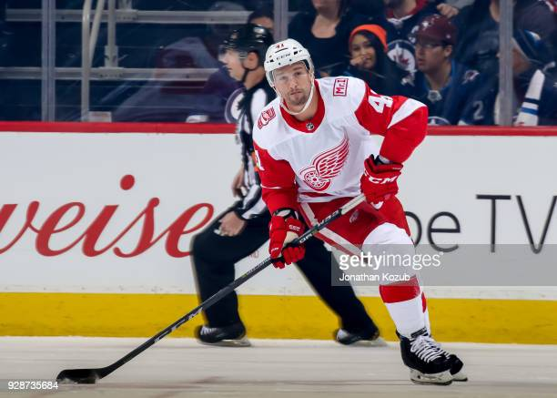 Luke Glendening of the Detroit Red Wings plays the puck up the ice during first period action against the Winnipeg Jets at the Bell MTS Place on...