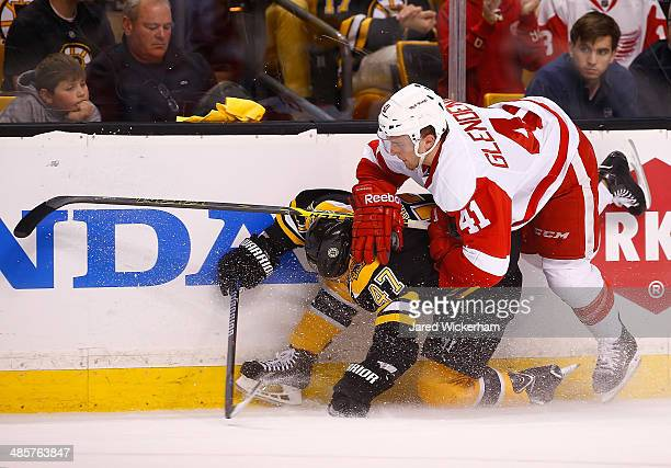 Luke Glendening of the Detroit Red Wings shoves Torey Krug of the Boston Bruins against the boards in the first period during the game at TD Garden...