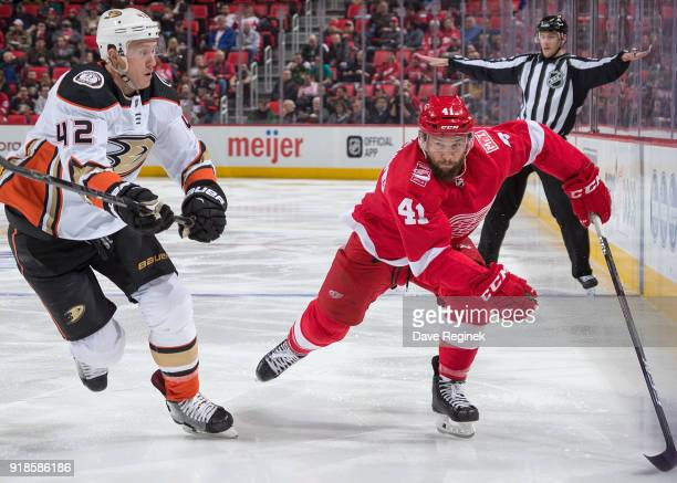 Luke Glendening of the Detroit Red Wings skates up ice next to Josh Manson of the Anaheim Ducks during an NHL game at Little Caesars Arena on...