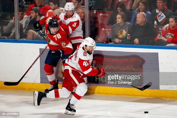 Luke Glendening of the Detroit Red Wings skates with the puck while teammate Nick Jensen ties up Maxim Mamin of the Florida Panthers at the BBT...