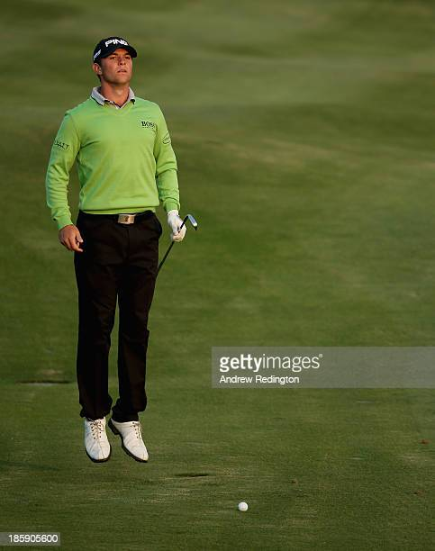 Luke Guthrie of the USA jumps to see the green before playing his second shot on the 18th hole during the third round of the BMW Masters at Lake...