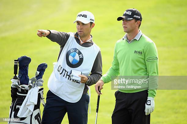 Luke Guthrie of the USA receives some advice from his caddie on the ninth hole during the third round of the BMW Masters at Lake Malaren Golf Club on...