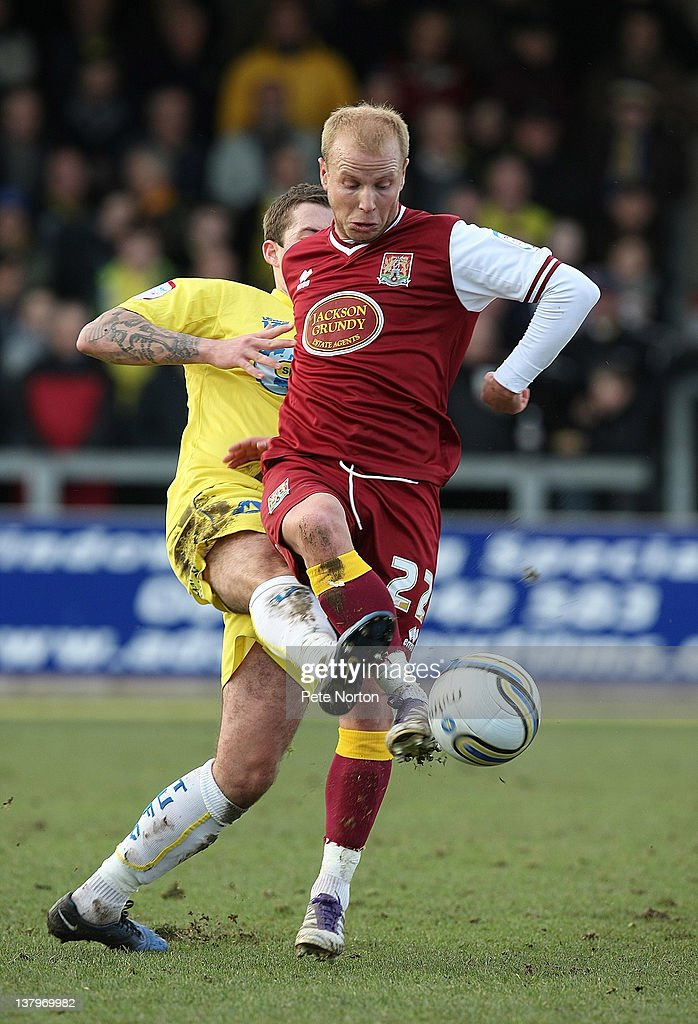 Luke Guttridge of Northampton Town controls the ball under pressure from Damon Lathrope of Torquay United during the npower League Two match between Torquay United and Northampton Town at Plainmoor on January 28, 2012 in Torquay, England.
