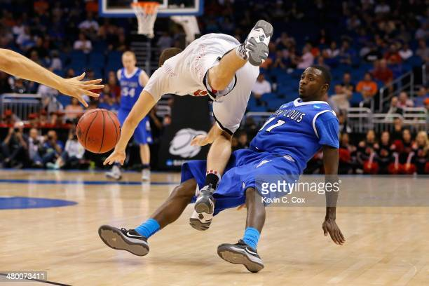 Luke Hancock of the Louisville Cardinals is called for traveling against Mike McCall Jr #11 of the Saint Louis Billikens in the second half during...