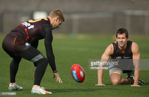 Luke Hodge of the Hawks coming back from a three week suspension watches Sam Mitchell of the Hawks bounce the ball like an umpire during a Hawthorn...