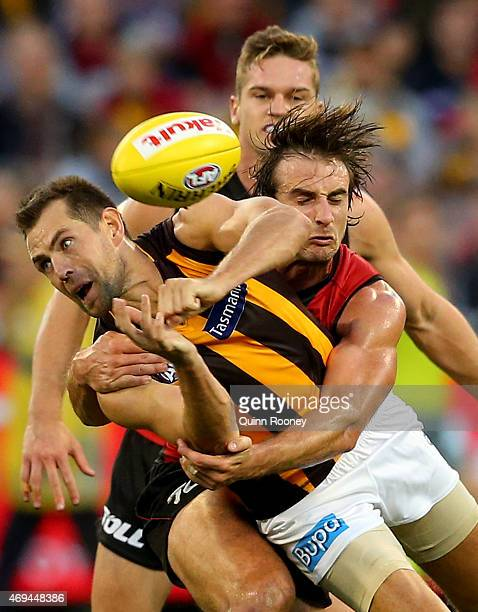 Luke Hodge of the Hawks handballs whilst being tackled by Jobe Watson of the Bombers during the round two AFL match between the Essendon Bombers and...