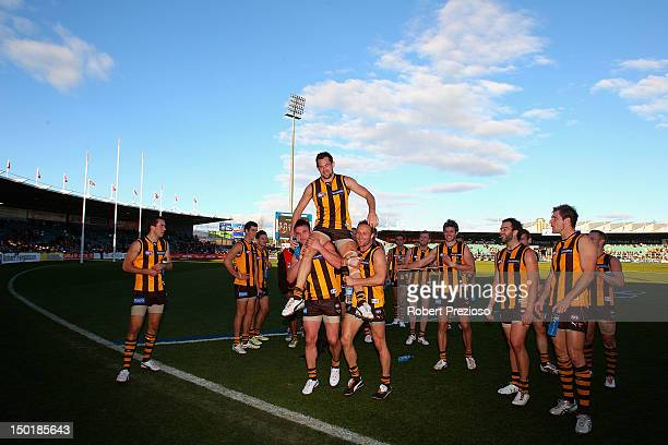 Luke Hodge of the Hawks is chaired off the ground by teammates after the round 20 AFL match between the Hawthorn Hawks and the Port Adelaide Power at...