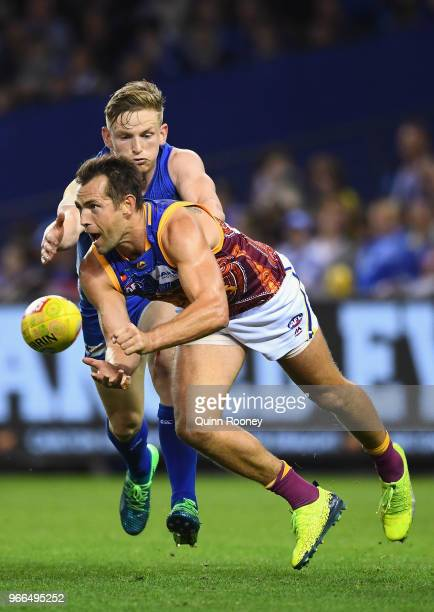 Luke Hodge of the Lions handballs whilst being tackled by Jack Ziebell of the Kangaroos during the round 11 AFL match between the North Melbourne...