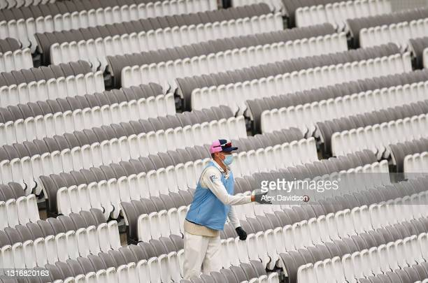 Luke Holman of Middlesex retrieves a ball out the stands whilst wearing PPE during Day Two of the LV= Insurance County Championship match between...