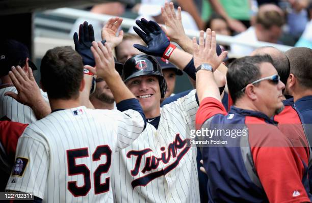 Luke Hughes of the Minnesota Twins celebrates a tworun home run against the Detroit Tigers in the fourth inning on August 28 2011 at Target Field in...