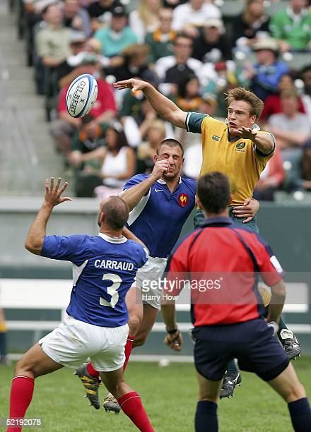 Luke Inman of Australia passes the ball under pressure from Jerome Guisset and Julien Carraud of France during the IRB 2005 USA Sevens Tournament...