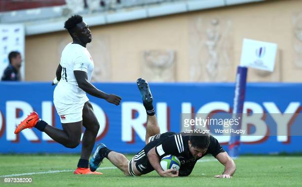 Luke Jacobson of New Zealand goes over for his try under pressure from Gabriel Ibitoye of England during the World Rugby U20 Championship final match...