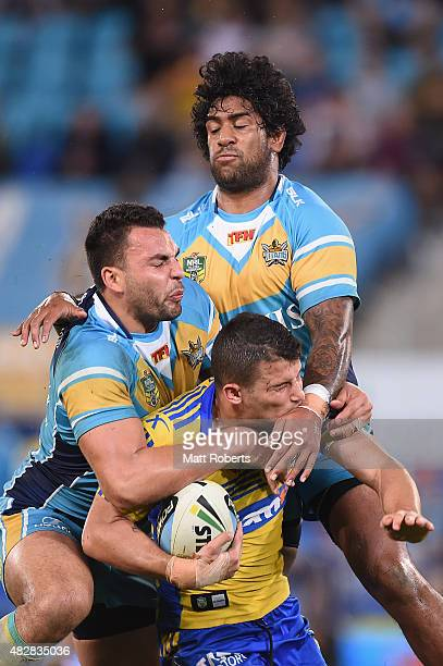 Luke Kelly of the Eels is tackled by Ryan James and Eddy Pettybourne of the Titans during the round 21 NRL match between the Gold Coast Titans and...