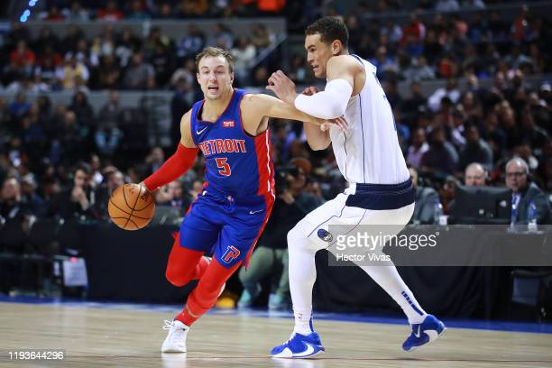 Luke Kennard of the Detroit Pistons handles the ball against Dwight Powell of the Dallas Mavericks during a game between Dallas Mavericks and Detroit...