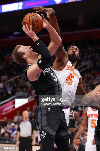 Luke Kennard of the Detroit Pistons tries to get a shot around DeAndre Jordan of the New York Knicks during the second half at Little Caesars Arena...