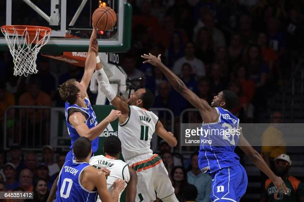 Luke Kennard of the Duke Blue Devils blocks a shot by Bruce Brown of the Miami Hurricanes at Watsco Center on February 25 2017 in Coral Gables Florida
