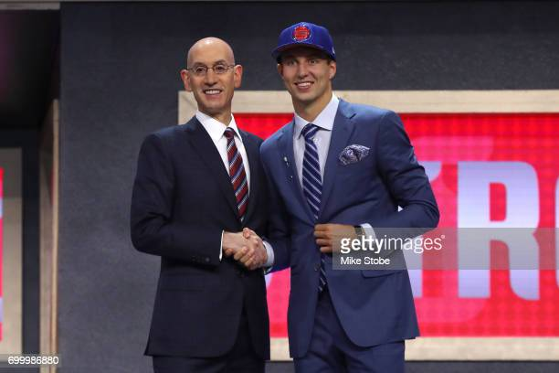 Luke Kennard walks on stage with NBA commissioner Adam Silver after being drafted 12th overall by the Detroit Pistons during the first round of the...