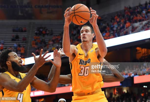 Luke Knapke of the Toledo Rockets controls a rebound over teammate Tre'Shaun Fletcher against the Syracuse Orange during the first half at the...