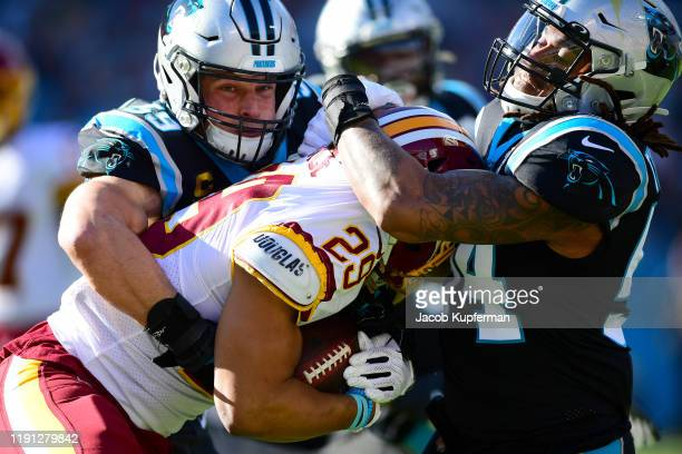 Luke Kuechly and Shaq Thompson of the Carolina Panthers bring down Derrius Guice of the Washington Redskins during the first quarter during their...