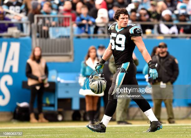 Luke Kuechly checks on teammate Taylor Heinicke of the Carolina Panthers after a play against the Atlanta Falcons in the second quarter during their...
