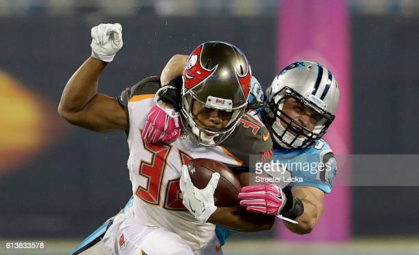 Luke Kuechly of the Carolina Panthers tackles Jacquizz Rodgers of the Tampa Bay Buccaneers in the 1st quarter during their game at Bank of America...
