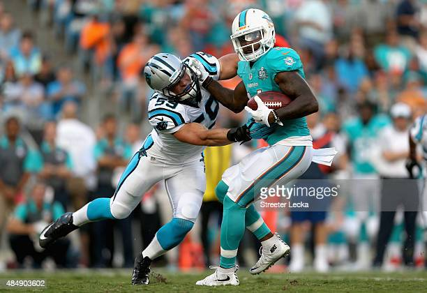 Luke Kuechly of the Carolina Panthers tackles Jarvis Landry of the Miami Dolphins during their game at Bank of America Stadium on August 22 2015 in...