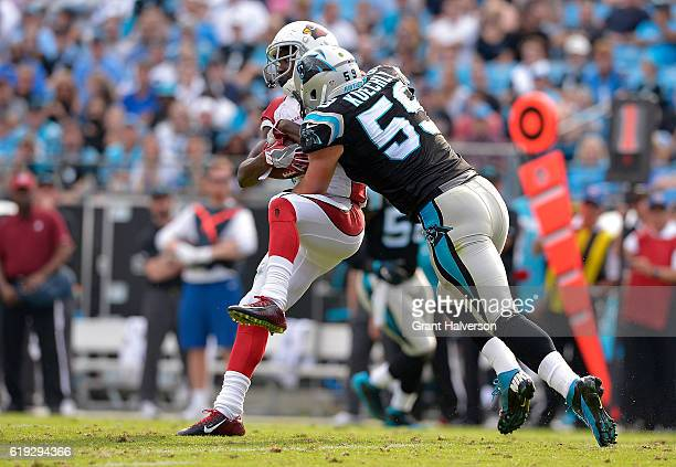 Luke Kuechly of the Carolina Panthers tackles John Brown of the Arizona Cardinals in the 4th quarter during the game at Bank of America Stadium on...