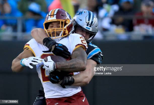 Luke Kuechly of the Carolina Panthers tries to stop Derrius Guice of the Washington Redskins during their game at Bank of America Stadium on December...