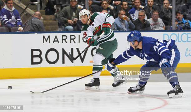 Luke Kunin of the Minnesota Wild fires a shot while being checked by Morgan Rielly of the Toronto Maple Leafs during an NHL game at Scotiabank Arena...