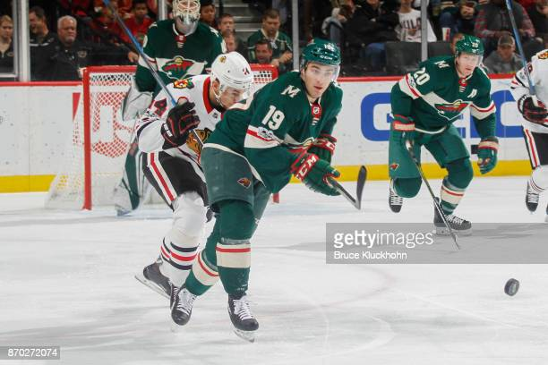 Luke Kunin of the Minnesota Wild passes the puck with Jan Rutta of the Chicago Blackhawks defending during the game at the Xcel Energy Center on...