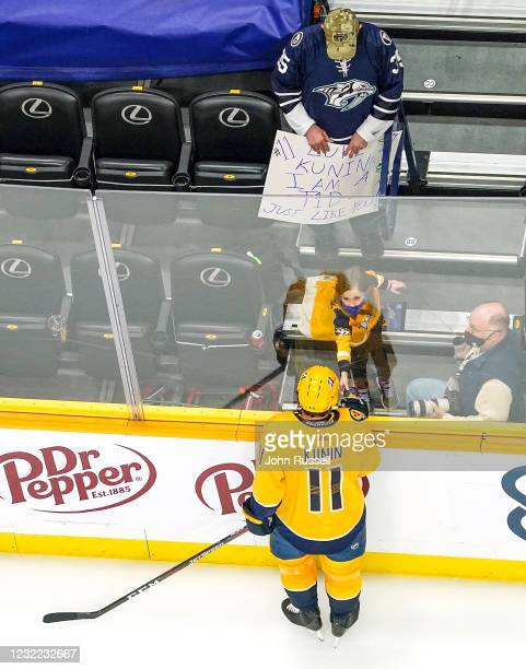 Luke Kunin of the Nashville Predators gives a puck to a young fan during warmups against the Tampa Bay Lightning at Bridgestone Arena on April 10,...