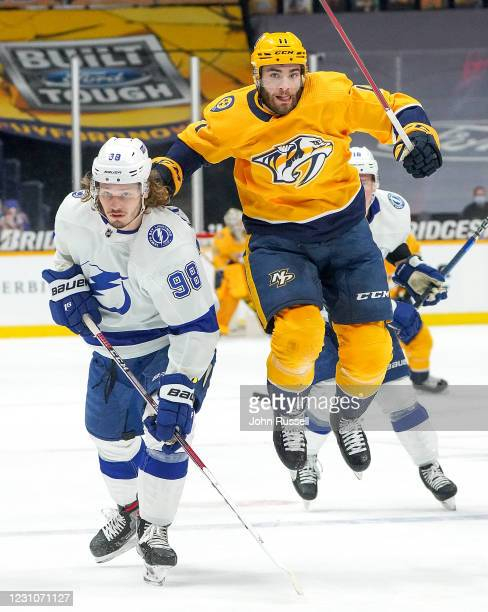 Luke Kunin of the Nashville Predators skates against Mikhail Sergachev of the Tampa Bay Lightning during the second period at Bridgestone Arena on...