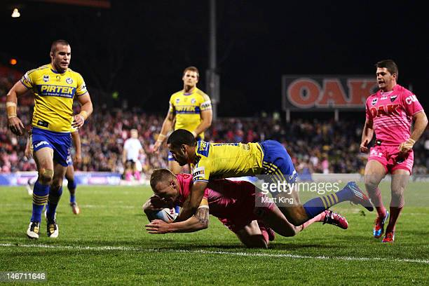Luke Lewis of the Panthers beats the tackle of Jarryd Hayne of the Eels to score a try during the round 16 NRL match between the Penrith Panthers and...