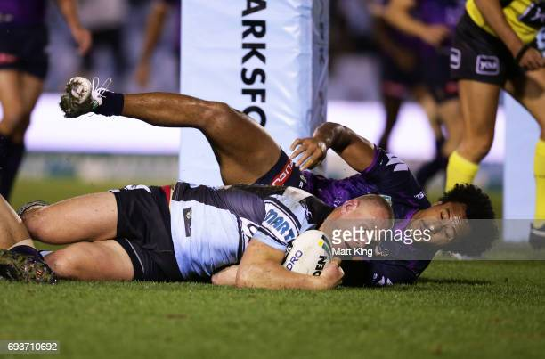Luke Lewis of the Sharks beats Felise Kaufusi of the Storm to score a try during the round 14 NRL match between the Cronulla Sharks and the Melbourne...