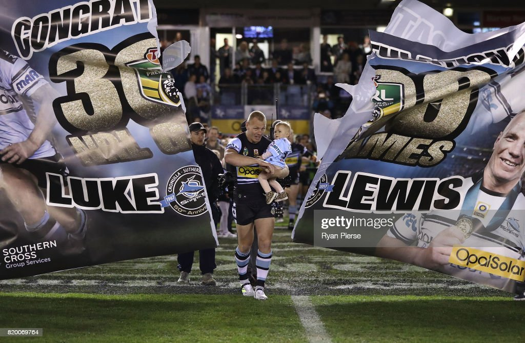 Luke Lewis of the Sharks breaks through the banner as he runs on to play his 300th game during the round 20 NRL match between the Cronulla Sharks and the South Sydney Rabbitohs at Southern Cross Group Stadium on July 21, 2017 in Sydney, Australia.