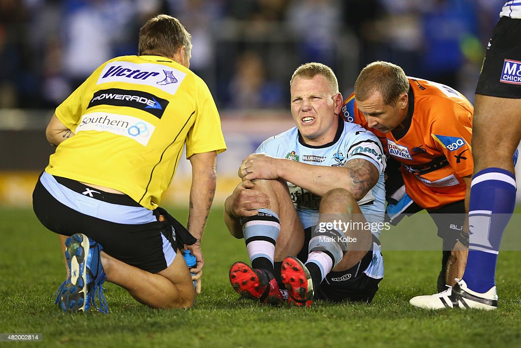 Luke Lewis of the Sharks grimaces as he receives attention for an injury during the round 20 NRL match between the Canterbury Bulldogs and the Cronulla Sharks at Belmore Sports Ground on July 26, 2015 in Sydney, Australia.
